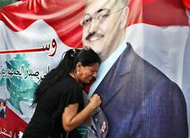 A woman mourns at a poster with an image of senior intelligence official Wissam al-Hassan during a protest against his killing, at Martyrs' square in downtown Beirut October 20, 2012. REUTERS/Ahmed Jadallah
