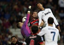 Raphael Varane (direita), do Real Madrid, pula para cabecear a bola disputada pelo goleiro Sergio Alvarez e Andres Tunez, do Celta, em partida neste sábado, em Madri.