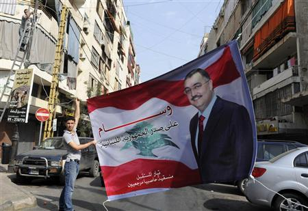 A Sunni Muslim man hangs up a poster with an image of senior intelligence official Wissam al-Hassan, in the Tariq al-Jadideh district in Beirut October 20, 2012. REUTERS/Hussam Shebaro