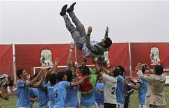 Tofan Harirod soccer players throw their coach in the air after beating Simorgh Ablorz in the final match of the Afghan soccer premier league in Kabul October 19, 2012. REUTERS/Omar Sobhani
