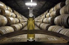 A bottle of cognac sits on an oak cask in a cellar where cognac is aged at the Remy Martin distillery in Cognac, southwestern France, October 8, 2012. REUTERS/Regis Duvignau