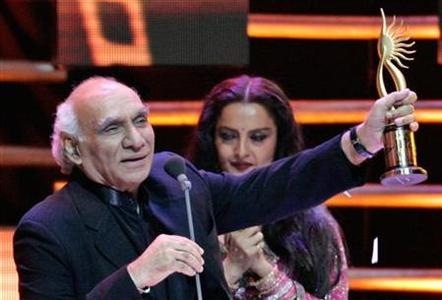 Bollywood director Yash Chopra holds up trophy at International Indian Film Academy Awards in Amsterdam June 11, 2005. REUTERS/Toussaint Kluiters