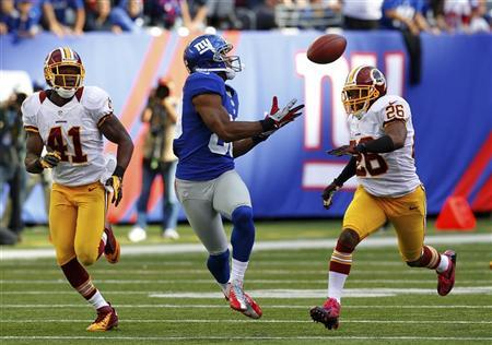 New York Giants Victor Cruz (C) catches the game winning touchdown between Washington Redskins Madieu Willims (L) and Josh Wilson (R) in the fourth quarter during their NFL football game in East Rutherford, New Jersey, October 21, 2012. REUTERS/Gary Hershorn