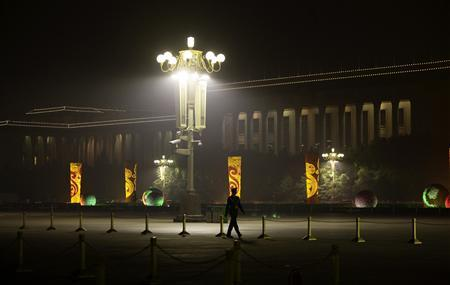 A paramilitary officer walks on the closed Tiananmen Square in front of the Great Hall of the People, the venue of the upcoming 18th National Congress of the Communist Party of China, on a hazy night in Beijing, in this October 8, 2012 file photo. REUTERS-Jason Lee-Files