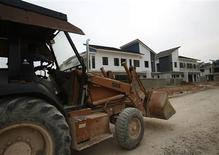An excavator drives past a cluster of uncompleted residential apartments at Nusajaya in the southern state of Johor in this September 14, 2012 file photo. REUTERS/Edgar Su