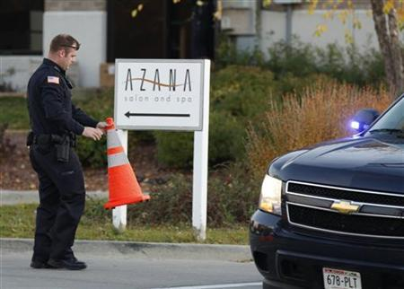 A policeman holds a traffic cone while guarding the Azana Salon and Spa in Brookfield, Wisconsin, October 21, 2012, where three people were killed and at least four injured in a shooting, Brookfield Police Chief Daniel Tushaus said at a news conference. REUTERS/John Gress
