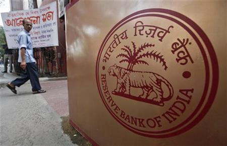 A man walks past a logo of the Reserve Bank of India (RBI) in front of its building in Kolkata May 21, 2012. REUTERS/Rupak De Chowdhuri/Files