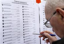 """Мужчина просматривает списки кандидатов в Координационный совет оппозиции у избирательного участка в Москве 21 октября 2012 года. Российская оппозиция начала выборы в свой новый руководящий орган, который кандидаты в его состав считают потенциальным """"теневым правительством"""", на сутки позже запланированного, жалуясь на хакерскую атаку. REUTERS/Maxim Shemetov"""
