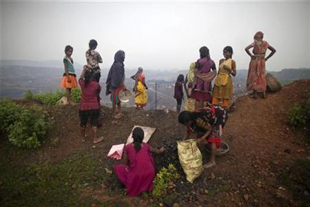 Local women stand atop of an open cast coal field as other collect coal at Dhanbad district in Jharkhand September 20, 2012. REUTERS/Ahmad Masood