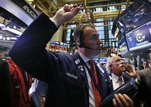 Трейдер работает в торговом зале биржи в Нью-Йорке, 5 октября 2012 года. Американские акции снизились в пятницу из-за слабых отчетов General Electric и McDonald's, но слегка поднялись за неделю. REUTERS/Mike Segar