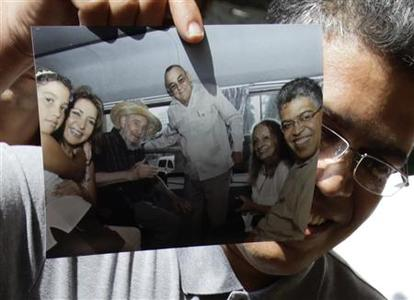Venezuela's former vice president Elias Jaua shows a picture of himself and former Cuban leader Fidel Castro, (3rd from L), in Havana October 21, 2012. REUTERS/Desmond Boylan