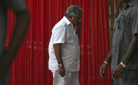 Kingfisher Airlines Chairman Vijay Mallya speaks on a mobile phone amid his security personnel on guard during a meeting with the debt-laden airline's pilots in New Delhi in this March 15, 2012 file photograph. REUTERS/Parivartan Sharma/Files