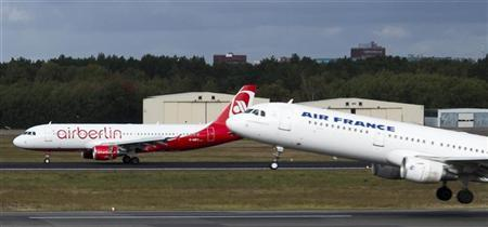 A plane of the French carrier Air France passes a plane of the German carrier Air Berlin during take-off at Tegel Airport in Berlin October 8, 2012. REUTERS/Thomas Peter