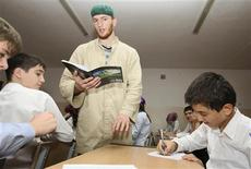 Islam Dzhabrailov (C), 21, speaks to pupils at a school in the Chechen capital of Grozny September 21, 2012. One of 420 teachers employed from madrasas to teach history of religion, Dzhabrailov is driving efforts by Chechen leader Ramzan Kadyrov to combat Islamist insurgency by implementing his own brand of Islam. In this Kadyrov has the backing of President Vladimir Putin, though some may harbor doubts about the man. Picture taken September 21, 2012. REUTERS/Stringer