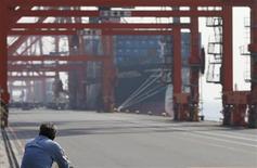 Мужчина смотрит на грузовой пароход в порту в Токио, 22 октября 2012 года. Экспорт из Японии сократился на 10,3 процента с начала 2012 года, что стало самым резким спадом после землетрясения в прошлом году, и это может вынудить Банк Японии снизить прогноз развития экономики и смягчить денежно-кредитную политику, говорят аналитики. REUTERS/Toru Hanai