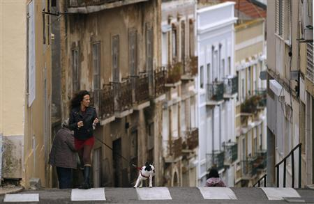 A woman walks her dog in Lisbon October 22, 2012. Portugal, already on a euro zone financial lifeline after being cut off from market borrowing, more than halved its budget deficit last year to 4.4 percent of GDP from 9.8 percent as a result of reforms, but its debt jumped to 108.1 percent from 93.5 percent. REUTERS/Rafael Marchante