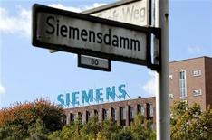 A street sign is pictured in front of a factory with the logo of Siemens AG company in Berlin October 9, 2012. REUTERS/Fabrizio Bensch (GERMANY - Tags: BUSINESS LOGO)