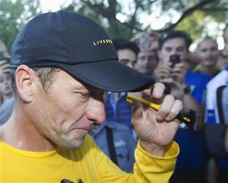 Lance Armstrong walks back to his car after running at Mount Royal park with fans in Montreal August 29, 2012. REUTERS/Christinne Muschi/Files