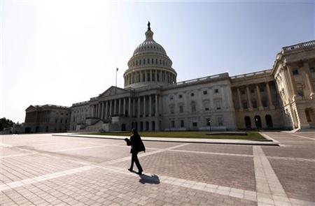 A woman walks past the U.S. Capitol in Washington September 25, 2012. REUTERS/Kevin Lamarque