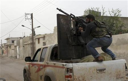 A member of the Free Syrian Army fires from a heavy machine gun towards pro-government forces in Salqin city in Idlib October 22, 2012. REUTERS/Asmaa Waguih