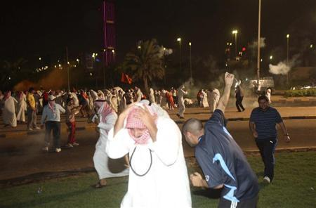 Protesters run from tear gas during a demonstration against proposed changes to election laws in Kuwait City October 21, 2012. REUTERS/Stringer