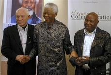 "Former South African President Nelson Mandela (C) arrives with veteran photographers Alf Khumalo (R) and Jurgen Schageberg for a photo exhibition and the launch of a book entitled ""The Meaning of Mandela"" at the Mandela Foundation in Johannesburg in this July 12, 2006 file photo. REUTERS/Antony Kaminju/Files"