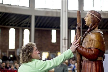Deborah Amell touches the statue in the likeness of Kateri Tekakwitha after the Mass of Thanksgiving in honor of Tekakwitha at the Shrine of Our Lady of Martyrs in Auriesville, New York, October 21, 2012. REUTERS/Jason Greene