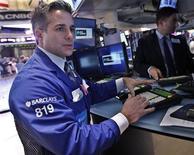 Трейдеры работают в торговом зале фондовой биржи в Нью-Йорке, 22 октября 2012 года. Американские фондовые рынки завершили сессию понедельника незначительным ростом на фоне сильной отчетности компаний, которая помогла инвесторам преодолеть волнение по поводу замедления роста мировой экономики. REUTERS/Brendan McDermid
