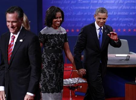 U.S. President Barack Obama (R) and first lady Michelle Obama walk past Republican presidential nominee Mitt Romney (L) as they leave the stage after the conclusion of the final U.S. presidential debate in Boca Raton, Florida October 22, 2012. REUTERS/Joe Skipper
