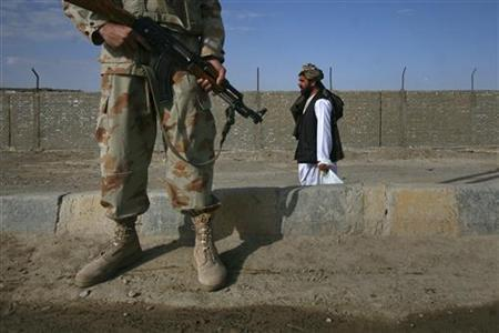 A man walks past an armed paramilitary soldier guarding the Pakistan-Afghanistan border crossing in Chaman November 28, 2011. REUTERS/Naseer Ahmed/Files