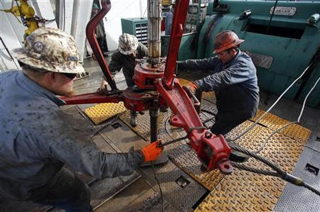 Roughnecks wrestle pipe on a True Company oil drilling rig outside Watford, North Dakota, October 20, 2012. REUTERS/Jim Urquhart