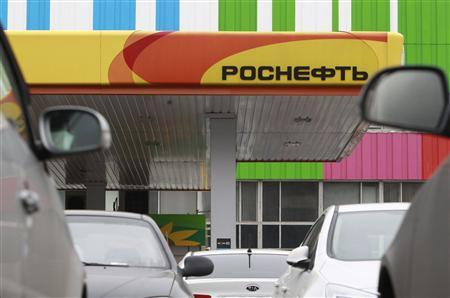 Parked cars stand outside a Russian oil company Rosneft petrol station near the Ostankino television tower in Moscow October 23, 2012. Rosneft tightened its grip on Russia's oil industry on Monday with a $55 billion deal to buy TNK-BP that also makes Britain's BP a one-fifth shareholder in the state-controlled company. REUTERS/Sergei Karpukhin