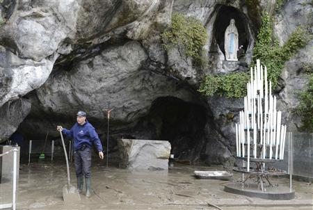 A man shovels mud from the flood waters of the River Gave outside the Roman Catholic shrine of the Grotto of Lourdes, southwestern France, October 21, 2012. REUTERS/Caroline Blumberg