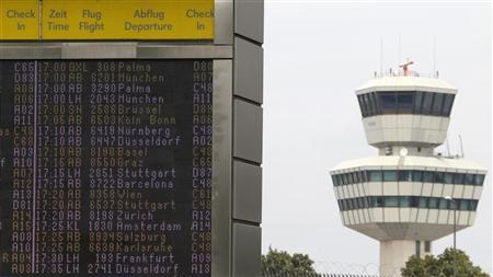 A departure board is seen next to the air traffic control tower at Berlin Tegel airport, August 3, 2011. REUTERS/Fabrizio Bensch