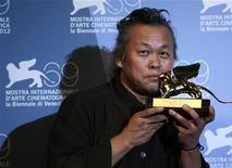 "South Korean director Kim Ki-duk kisses the Golden Lion prize for best movie ""Pieta"" at the 69th Venice Film Festival in Venice September 8, 2012. REUTERS/Tony Gentile"