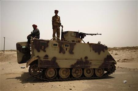 Army soldiers are seen atop an armoured personnel carrier, securing a road near the southern Yemeni city of Zinjibar June 21, 2012. REUTERS/Khaled Abdullah/Files