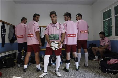 Players of the local Voukefalas soccer team wearing T-shirts displaying the logos of their sponsors, luxury brothels owned by Soula Alevridou, pose in the city of Larissa about 320 km (200 miles) north of Athens October 20, 2012. REUTERS/John Kolesidis
