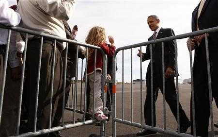 A little girl waves as U.S. President Barack Obama walks over to greet supporters upon his arrival in Dayton, Ohio October 23, 2012. REUTERS/Kevin Lamarque