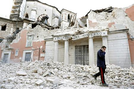 An Italian military carabinieri walks on debris past destroyed buildings after an earthquake, in downtown Aquila, in this April 6, 2009 file photo. REUTERS/Alessandro Bianchi/Files