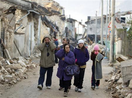 A family walks past rubbles from damaged buildings the morning after an earthquake struck the Italian village of Onna, in this April 7, 2009 file photo. REUTERS/Chris Helgren /Files