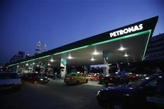 Motorists queue to fill natural gas at a Petronas station with its landmark Petronas Twin Towers headquarters in the background, in Kuala Lumpur February 4, 2012. REUTERS/Bazuki Muhammad
