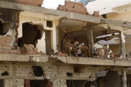 Soldiers are seen in a building damaged during fighting between the army and al Qaeda-linked militants in Zinjibar, the provincial capital of Yemen's southern province of Abyan, after the army retook it from the militants June 18, 2012. REUTERS/Khaled Abdullah