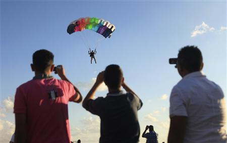 People take photographs as a man parachutes during a festival to celebrate Libya's first anniversary of its ''liberation'' from Muammar Gaddafi in Benghazi October 23, 2012. REUTERS/Esam Al-Fetori