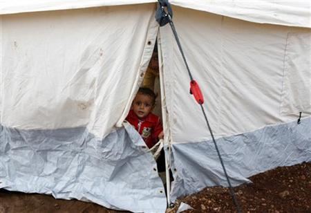 A refugee child looks out from a tent in a refugee camp in Atimeh, on the Syrian-Turkish border of the Idlib Governorate, October 23, 2012. REUTERS/Asmaa Waguih