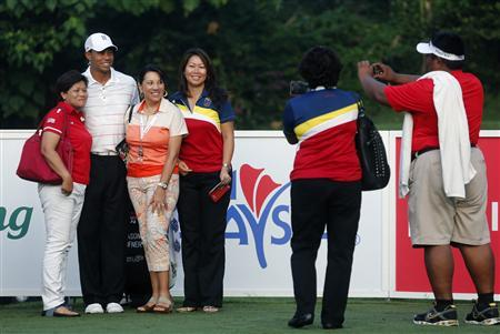 Fans pose wih Tiger Woods (2nd L) of the U.S. as he plays in the Pro-Am ahead of the Malaysia's Asia Pacific Classic golf tournament in Kuala Lumpur October 24, 2012. REUTERS/Bazuki Muhammad