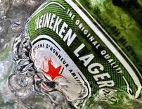 Бутылка пива Heineken лежит в ведре со льдом в Сингапуре, 10 мая 2012 года. Выручка третьей в мире пивоваренной компании Heineken NV превзошла прогнозы в третьем квартале 2012 года благодаря росту продаж в Северной и Южной Америках, Восточной Европе и Африке, а также повышению цен. REUTERS/Matthew Lee