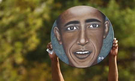 A supporter holds up an image of U.S. President Barack Obama at a campaign rally in Dayton, Ohio October 23, 2012. REUTERS/Kevin Lamarque