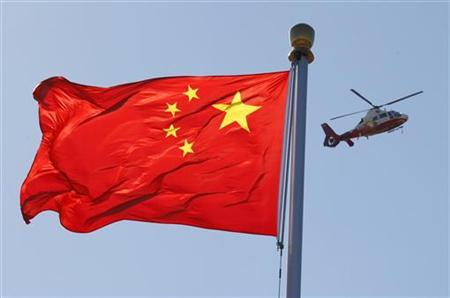 A China Central Television (CCTV) helicopter flies over the Chinese national flag in Tiananmen Square October 9, 2012. REUTERS/David Gray