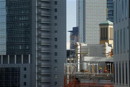 Workers at the construction site of a new convention centre are seen between skyscrapers near the fairground in Frankfurt, October 8, 2012. REUTERS/Kai Pfaffenbach