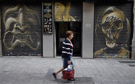 A woman walks past a partially closed tattoo shop in central Madrid October 2, 2012. REUTERS/Sergio Perez
